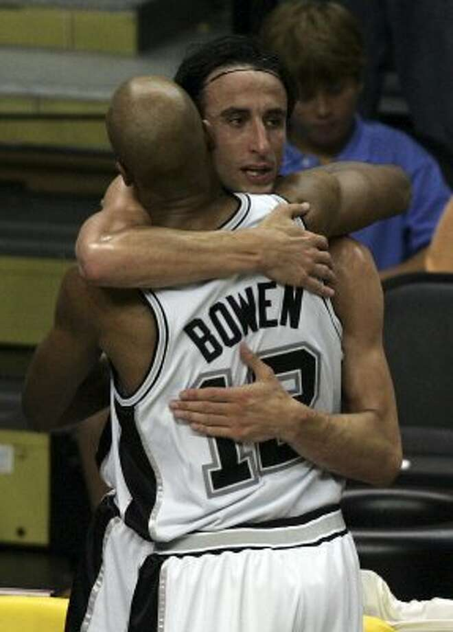 Spurs' Manu Ginobili hugs teammate Bruce Bowen in the closing moments of the fourth quarter of game two of the NBA Finals at the SBC Center on Thursday, June 9, 2005. Bowen hit four three-pointers to help lift the Spurs over the Pistons and capture game 2 97-76. (Kin Man Hui/staff) (SAN ANTONIO EXPRESS-NEWS)