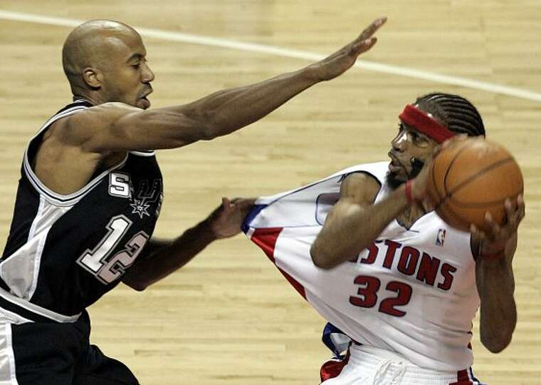 San Antonio Spurs' Bruce Bowen (12) holds on to Detroit Pistons' Richard Hamilton (32) during the fi