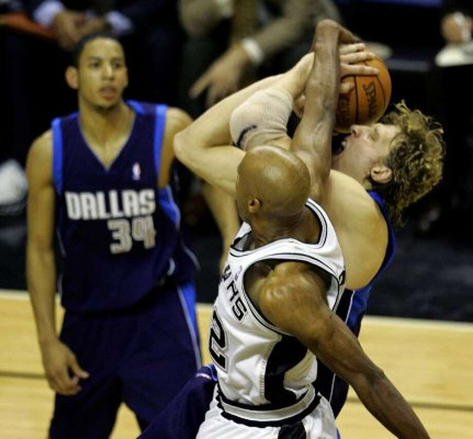 Spurs Bruce Bowen blocks the shot of Mavericks Dirk Nowitzki late in the fourth quarter forcing a jump ball during the fifth game in the Western Conference semi-finals at the AT&T Center on Wednesday, May 17, 2006. Following the jump ball was another scramble for the loose ball resulting in yet another jump ball. Time finally ran out for the Mavs with the Spurs winning 98-97.( JERRY LARA ) (SAN ANTONIO EXPRESS-NEWS)