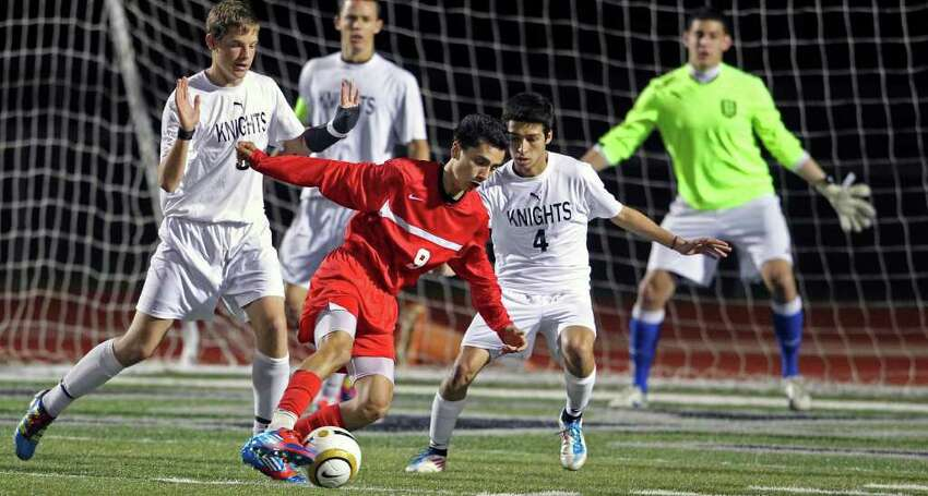 Judson's Andrew Gomez positions himself for a shot on goal while Steele's Zach Hamilton (9) and James Montalbo guard as the Knights host the Rockets on Tuesday, March 20, 2012.