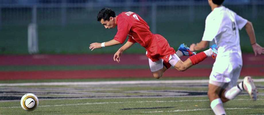 Judson's Andrew Gomez flies toward the ground after being fouled by Steele goalkeeper Jose Vazquez, resulting in a penalty kick and score as the Knights host the Rockets on Tuesday, March 20, 2012. Photo: TOM REEL, San Antonio Express-News / San Antonio Express-News
