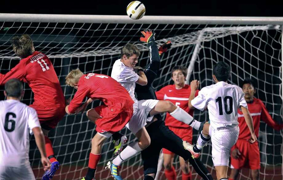 Steele's Zach Hamilton fouls Judson goalkeeper Alex Diehl as the Knights host the Rockets on Tuesday, March 20, 2012. Photo: TOM REEL, San Antonio Express-News / San Antonio Express-News