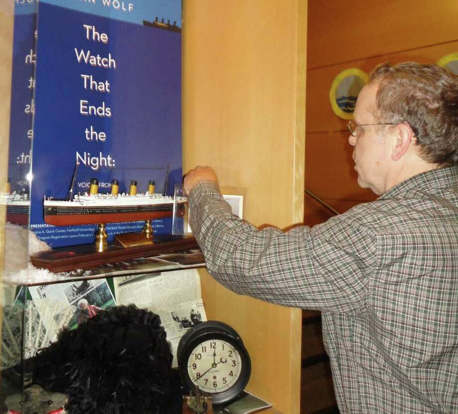 "Sandy Clarkson, an acquaintance of Millvina Dean, the youngest survivor of the Titanic sinking, on Monday places a model of the ill-fated ship in a display case at the Fairfield Public Library, where it will remain through the library's ""One Book, One Town"" initiative, which this year is focusing on ""The Watch that Ends the Night: Voices from the Titanic."" Photo: Meg Barone / Fairfield Citizen freelance"