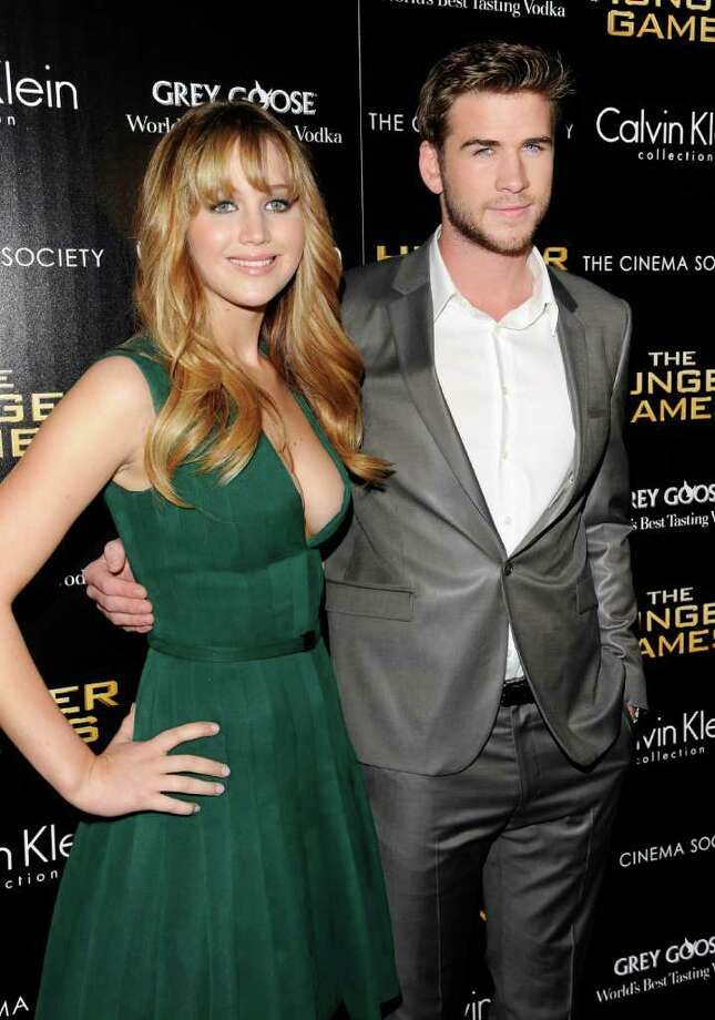 "Actors Jennifer Lawrence, left, and Liam Hemsworth attend a special screening of ""The Hunger Games"" hosted by The Cinema Society and Calvin Klein Collection at SVA Theatre on Tuesday, March 20, 2012 in New York. Photo: Evan Agostini, AP / AGOEV"