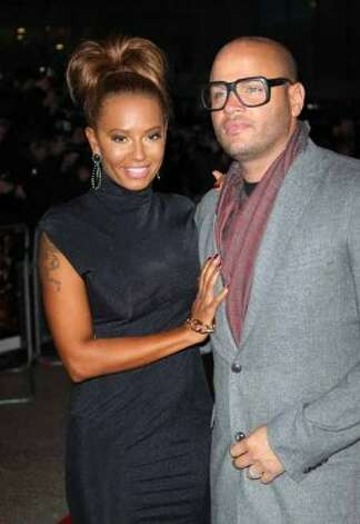 "Melanie Brown, left, and husband Stephen Belafonte arrive at ""The Hunger Games"" U.K. film premiere at the O2 Arena in London, Wednesday, March 14, 2012."