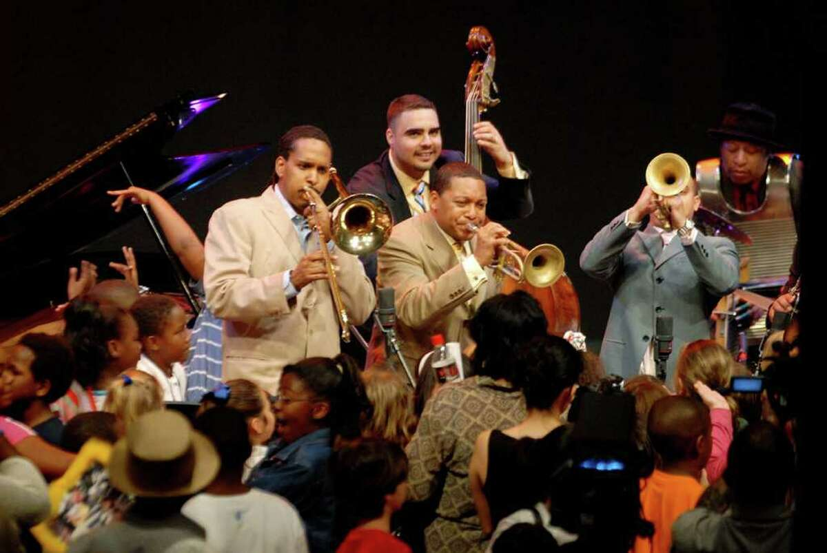 Wynton Marsalis (center trumpet) with member of his Lincoln Center Jazz Orchestra Vincent Gardener (left trombone) Carlos Henriquez (rear bass) and Irvin Mayfield (right trumpet) perform for New Orleans school children during a Jazz for Young People program at the Convention Center in New Orleans, Louisiana Friday April 21, 2006. 6mpfas1k