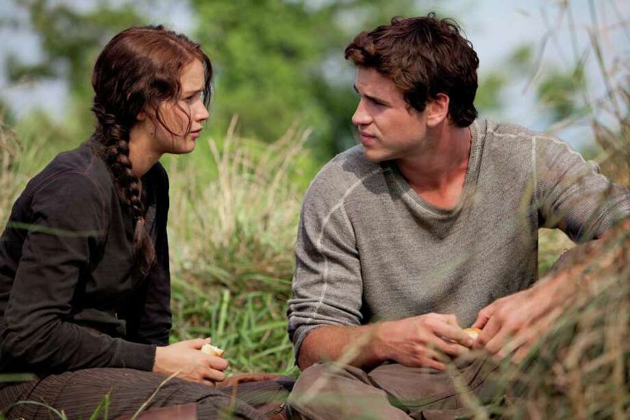 "In this image released by Lionsgate, Jennifer Lawrence portrays Katniss Everdeen, left, and Liam Hemsworth portrays Gale Hawthorne in a scene from ""The Hunger Games."" (AP Photo/Lionsgate, Murray Close) Photo: Murray Close"