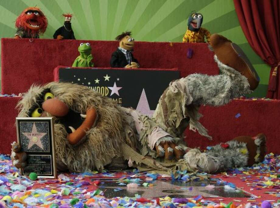 Jim Henson' puppet character, Muppets' Sweetums, the ogre poses with The Muppets as they are honored with a Star on the Hollywood Walk of Fame in Los Angeles on Tuesday, Mar. 20, 2012. (Damian Dovarganes / Associated Press)