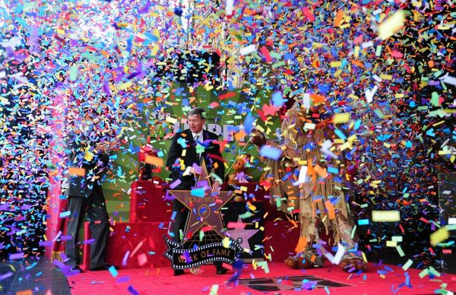 "Beneath a sea of confetti, Leron Gubler (C), President and CEO of the Hollywood Chamber of Commerce, and Sweetums (R) unveil the Muppets Star on Hollywood's Walk of Fame in front of the El Capitan Theater in Hollywood on March 20, 2012 in California. Since ""The Muppet Show"" began in 1976, they have been embraced by audiences worldwide and several Muppets were on hand for the ceremony including Kermit the frog, Miss Piggy, Fozzie, Gonzo, Animal, Pepe, Sweetums and the newest Muppet, Walter.     (FREDERIC J. BROWN / AFP/Getty Images)"