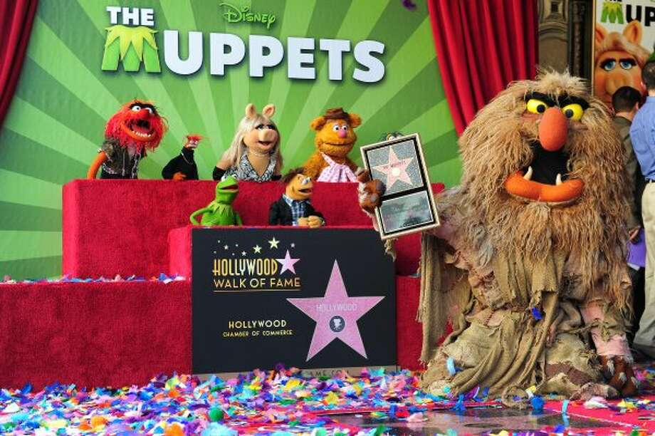 "Sweetums holds a plaque honouring the Muppets at the unveiling of their Star on Hollywood's Walk of Fame  in front of the El Capitan Theater in Hollywood on March 20, 2012 in California. Since ""The Muppet Show"" began in 1976, they have been embraced by audiences worldwide and several Muppets were on hand for the ceremony including Kermit the frog, Miss Piggy, Fozzie, Gonzo, Animal, Pepe, Sweetums and the newest Muppet, Walter. (FREDERIC J. BROWN / AFP/Getty Images)"
