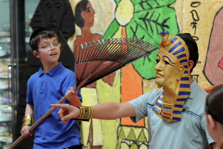 Eli Kochman of Albany, 12, dressed as aPharaoh, right, is cooled by a makeshift fan, a rake, by Amiel Ehrlich, 12 as they and fellow students from the Maimonides Hebrew Day School re-enact the exodus of the Jews from Egypt. The students from Albany then saw a demonstration of matzo making at Price Chopper in Colonie.  A member of the family who runs Streit's, a company from New York City that has made matzo since 1925, was in attendance. (Philip Kamrass / Times Union ) Photo: Philip Kamrass / 00016891A