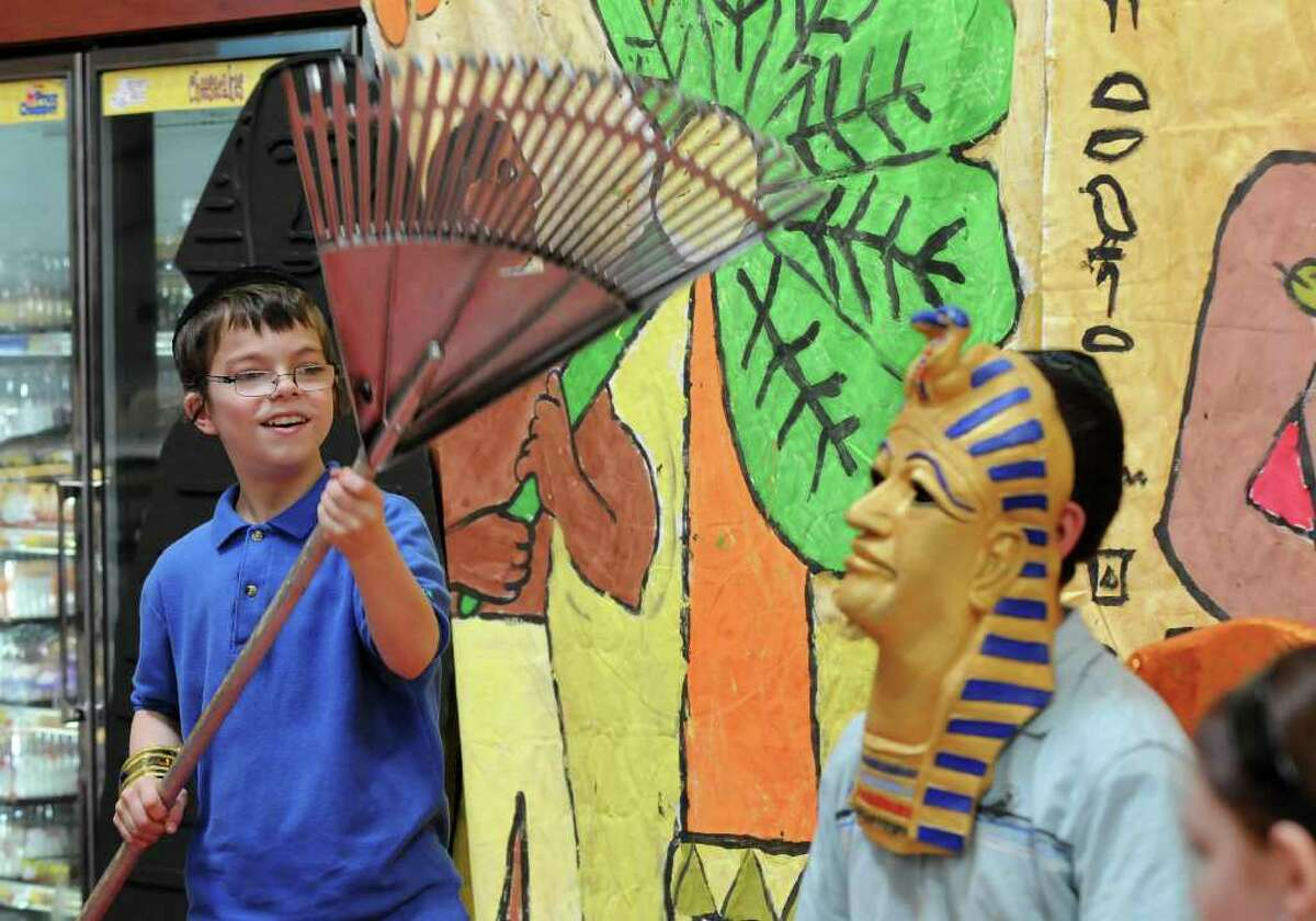 Eli Kochman of Albany, 12, dressed as aPharaoh, right, is cooled by a makeshift fan, a rake, by Amiel Ehrlich, 12 as they and fellow students from the Maimonides Hebrew Day School re-enact the exodus of the Jews from Egypt. The students from Albany then saw a demonstration of matzo making at Price Chopper in Colonie. A member of the family who runs Streit's, a company from New York City that has made matzo since 1925, was in attendance. (Philip Kamrass / Times Union )