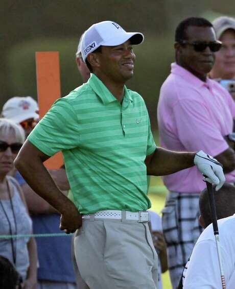 Tiger Woods grimaces and holds his hand against his back after he felt a twinge in his lower back during his back swing on his tee shot on the sixth hole during the Pro-Am round at the Arnold Palmer Invitational golf tournament at Bay Hill, Wednesday, March 21, 2012, in Orlando, Fla. Photo: AP