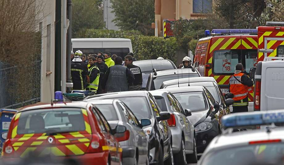 Police officers and firefighters stand next to the building where the suspected killer is holed-up  in Toulouse Wednesday March 21, 2012 .  After a pre-dawn raid erupted into a firefight, French riot police pressed Wednesday for the surrender of a holed-up gunman who is suspected in seven killings and claiming allegiance to al-Qaida. A prosecutor said the gunman was planning to kill another soldier imminently. Photo: Remy De La Mauvinere, Associated Press