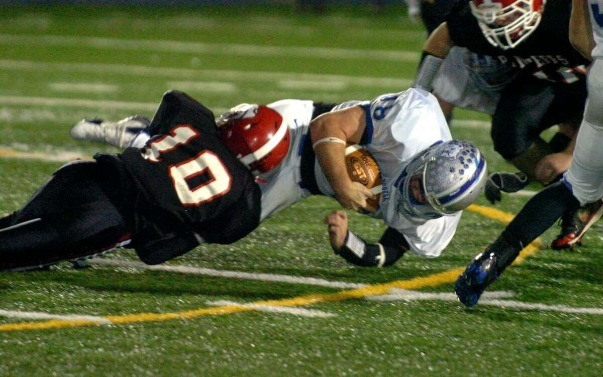 Bunnell QB #18 Zach Thomas gets brought down by Masuk's #10 Shawn Flynn, during football action in Stratford, Conn. on Saturday Nov. 14, 2009.