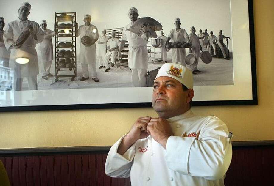 "Master baker Fernando Padilla fixing his jacket at Boudin Bakery on 10th Ave.  Fernando apprenticed with former Boudin owner ""Papa Steve"" Giraudo at 17 years old. (Liz Hafalia / The Chronicle)"
