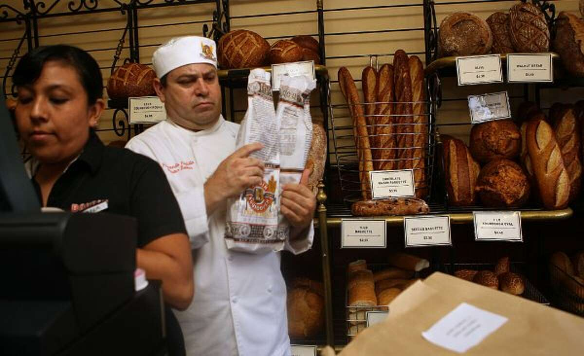 Diana Flores (left) working behind the counter as master chef Fernando Padilla packages some bread. (Liz Hafalia / The Chronicle)