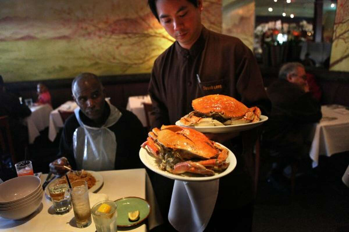 Victor Mayo (left) and his wife being served dungeness crab roasted with garlic sauce at Thanh Long (Liz Hafalia / The Chronicle)