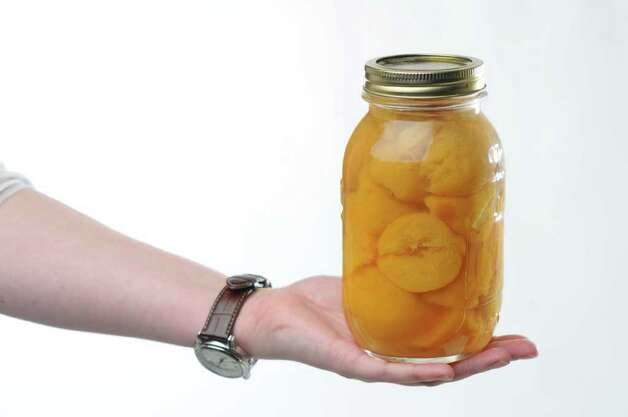 A jar of peaches for a food swap from a member of the From Scratch Club, in the Times Union photography studio on Tuesday March 13, 2012 in Colonie, N.Y.   (Philip Kamrass / Times Union ) Photo: Philip Kamrass / 00016763A