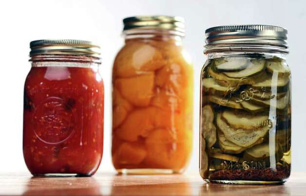 Jars of stewed tomatoes, left, peaches, center, and pickles, right, for a food swap from members of the From Scratch Club, in the Times Union photography studio on Tuesday March 13, 2012 in Colonie, N.Y.   (Philip Kamrass / Times Union ) Photo: Philip Kamrass / 00016763A