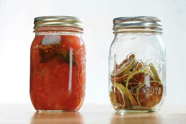 Jars of stewed tomatoes, left, and dried limes, right, for a food swap from members of the From Scratch Club, in the Times Union photography studio on Tuesday March 13, 2012 in Colonie, N.Y.   (Philip Kamrass / Times Union ) Photo: Philip Kamrass / 00016763A