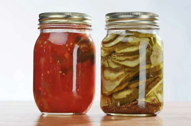 Jars of stewed tomatoes, left, and pickles, right, for a food swap from members of the From Scratch Club, in the Times Union photography studio on Tuesday March 13, 2012 in Colonie, N.Y.   (Philip Kamrass / Times Union ) Photo: Philip Kamrass / 00016763A