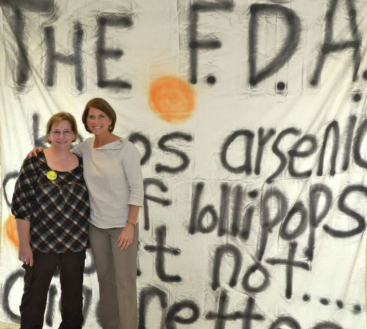 """Janice Marzano, director of The Depot, and First Selectman Jayme Stevenson stand in front of the Kick Butts Day wall hanging which reads, """"The FDA keeps arsenic out of lollipops but not...cigarettes!"""""""