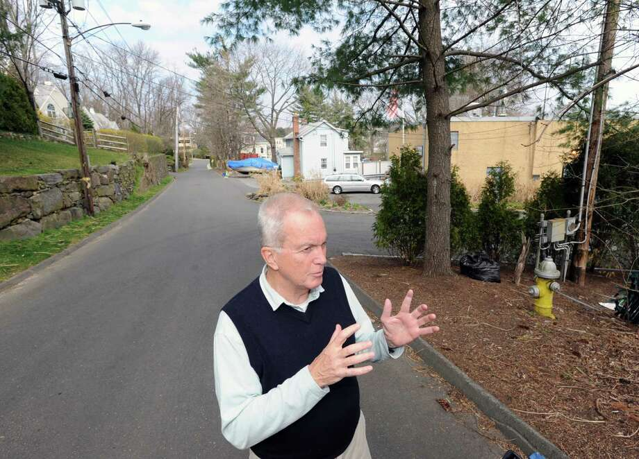 Mike Warner, stands on Spring Street as he speaks to a reporter about proposed developments in his central Greenwich neighborhood Wednesday, March 21, 2012. One of the developments being considered by the Planning and Zoning Commission includes the creation of an expanded Lexus of Greenwich service center that would turn a car storage  lot into a new three-story service facility with 24 service bays on Old Track Road. Wagner lives on Spring Street, which runs paraellel to Old Track Road, and is against the dealership expansion. Photo: Bob Luckey / Greenwich Time