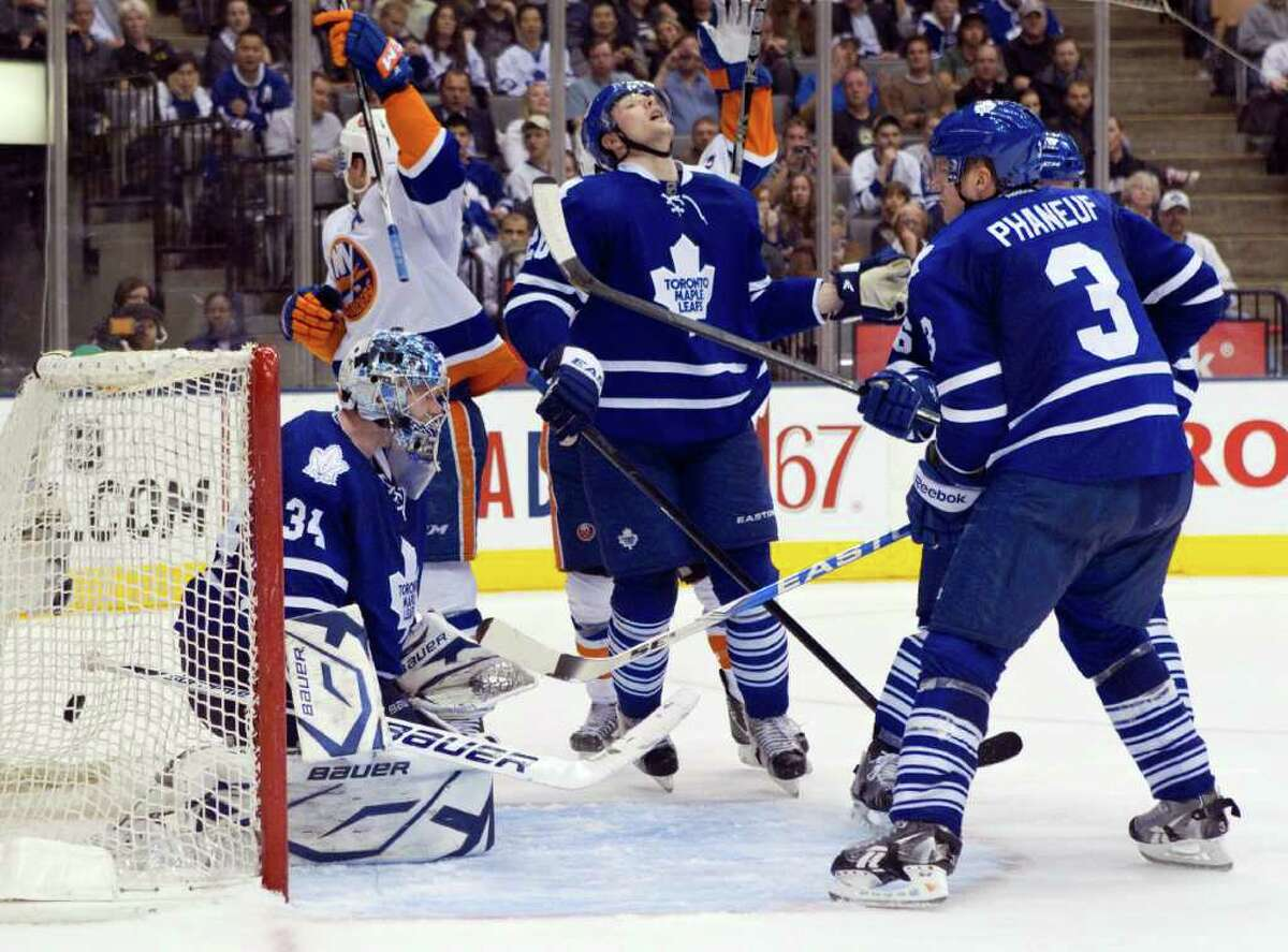 Toronto Maple Leafs' David Steckel, center, reacts as New York Islanders' Matt Moulson (obscured) scored his team's fourth goal as Maple Leaf's goaltender James Reimer, left, and captain Dion Phaneuf (3) look on during third period NHL hockey action in Toronto on Tuesday, March 20, 2012. At second left is Islanders' John Tavares. (AP Photo/The Canadian Press, Chris Young)