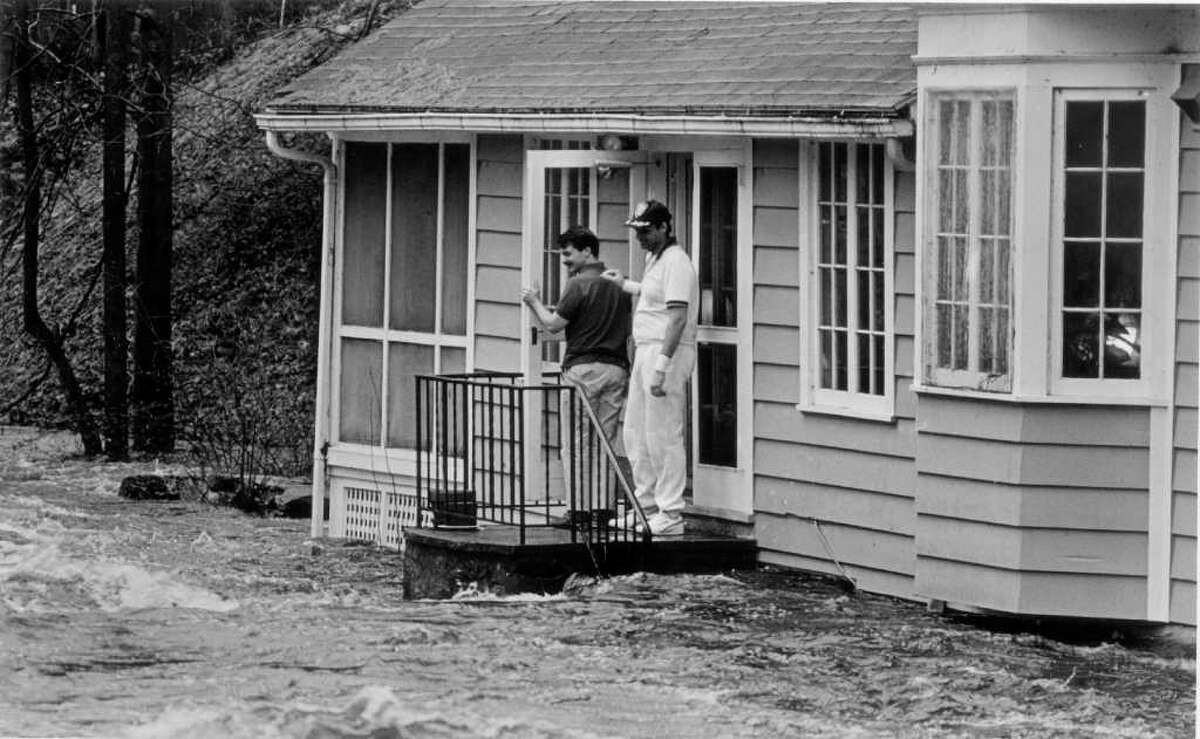 April 4, 1987: John Brodie and his brother-in-law. Doug Lynn, watch the rising waters of the Rippowam River cover five steps of Brodie's back stairs at his home on Maltbie Avenue after a spring storm drenched the region.