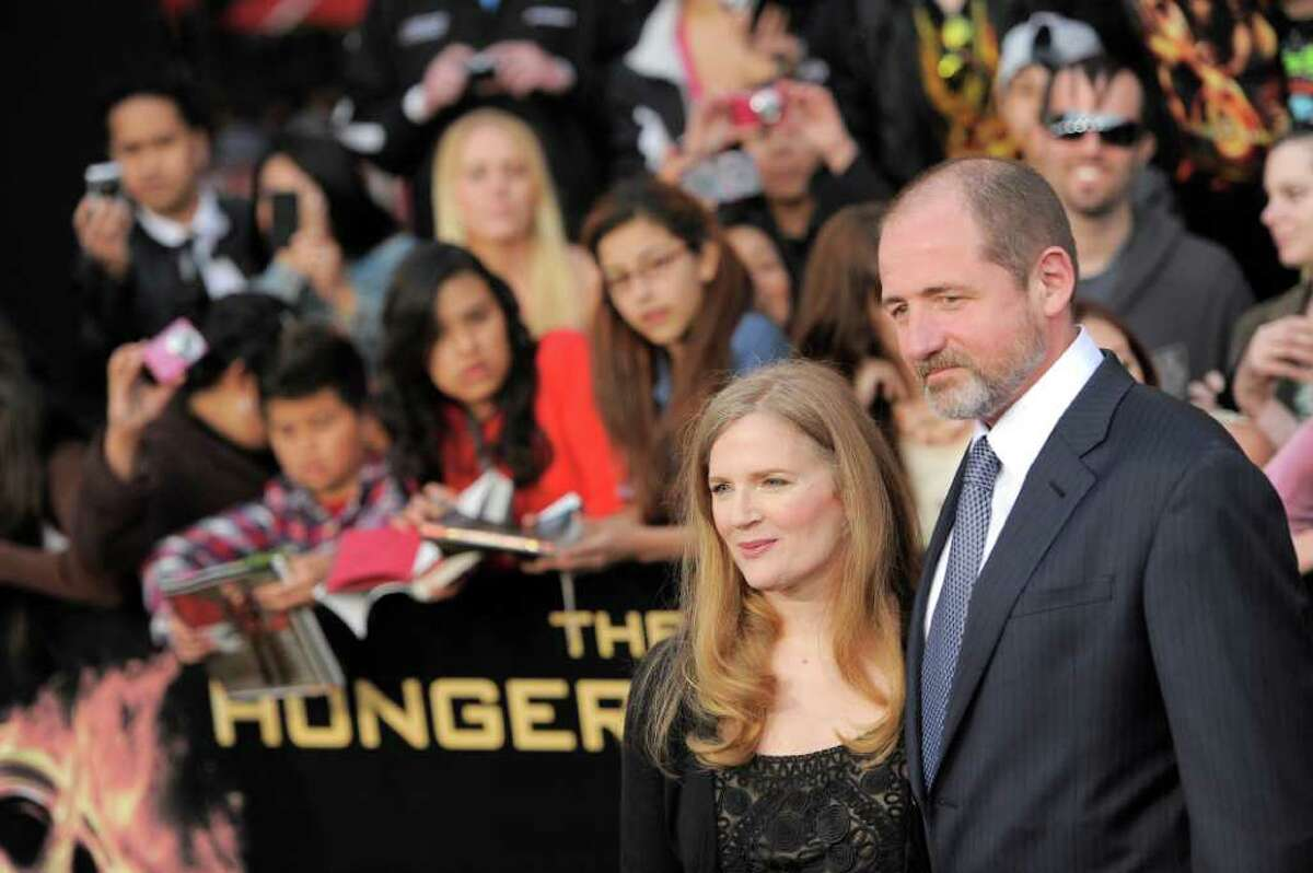 """Suzanne Collins and guest arrive at the world premiere of """"The Hunger Games"""" on Monday March 12, 2012 in Los Angeles. (AP Photo/Chris Pizzello)"""