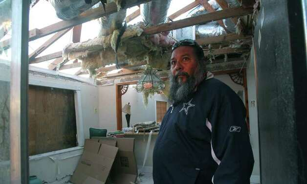 Contractor Paul Camacho assesses the damage to a storm-ravaged home on Texas 173 west of Devine. Camacho said he was donating his time for repairs. Photo: John Davenport, San Antonio Express-News