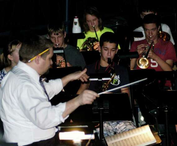 "SPECTRUM/NMHS band director David Syzdek conducts the pit orchestra during New Milford High School rehearsal for its all-school musical, ""42nd Street,"" March 19, 2012. Photo: Norm Cummings"