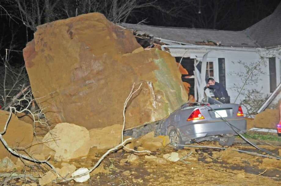 Tim Pfaff checks out the damage to his house and car, where a boulder landed after it broke free Tuesday night from a nearby hillside in Athens, Ohio, early Wednesday morning, March 21, 2012. The boulder crushed two vehicles, damaged a house, knocked down utility poles and damaged an underground water line, but no one was injured. Photo: AP