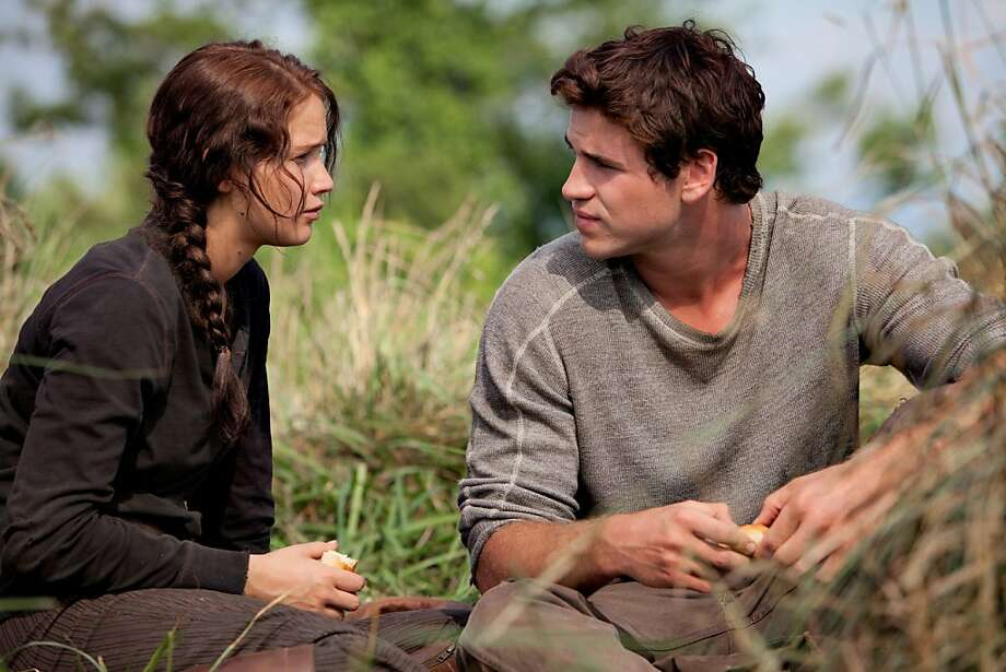 "Katniss Everdeen (Jennifer Lawrence, left) and Gale Hawthorne (Liam Hemsworth) star in ""The Hunger Games."" (Courtesy Murray Close/MCT) Photo: Handout, McClatchy-Tribune News Service"