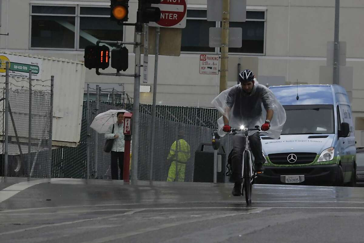 A bicyclist's poncho blows around him as he rides down Beale Street in the rain on Wednesday, December 8, 2010 in San Francisco, Calif.