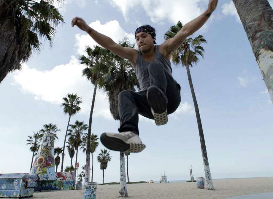 "Michael ""Frosti"" Zernow, a parkour athlete and instructor, shows some simple exercises for practicing the sport. He demonstrates the tic-tac, a move that kicks the athlete off of a wall or other solid object. Photo: Myung J. Chun / Los Angeles Times"