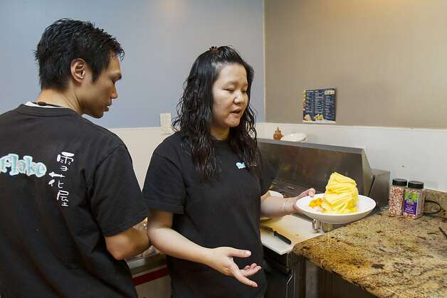 Snowflake owner Janice Kou, center, carries a plate of Tropic Mango shave ice at their store in Pleasanton, Calif. on Thursday, March 15, 2012. Snowflake is one of many asian dessert cafes that serves flavored shaved ice, an increasingly popular Taiwanese dessert in the Bay Area. Founded by husband and wife team Janice and Jeff Kou in 2011 after more than year of research, Snowflake is said to be the only Bay Area dessert cafe that makes their own flavored ice blocks in-house, 14 in all, while taking customers' unique flavor requests such as taro, ginger, yogurt and black sesame. Photo: Stephen Lam, Special To The Chronicle