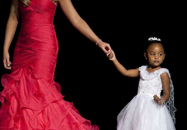 Little Princess Saaliaya Astorga, 2, is lead by the hand across the stage on Sunday during the Miss San Francisco Beauty Pagent. Beauty Pageant contestants from across the Bay Area met at the Ruth Asawa School of the Arts, Dan Kryston Memorial Theater on Sunday for the annual Miss San Francisco preliminary competition for Miss California. Photo: Kevin Johnson, The Chronicle