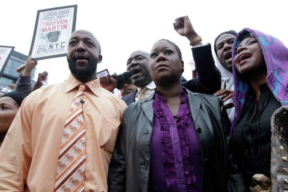 Trayvon Martin's parent's Tracy Martin, left, and Sybrina Fulton, center, are joined by an unidentified woman during the Million Hoodie March in Union Square Wednesday, March 21, 2012 in New York. A few hundred people are marching in New York City in memory of Trayvon Martin, a black teenager shot to death by a Hispanic neighborhood watch captain in Florida. The teenager was unarmed and was wearing a hoodie. (AP Photo/Mary Altaffer) Photo: Mary Altaffer
