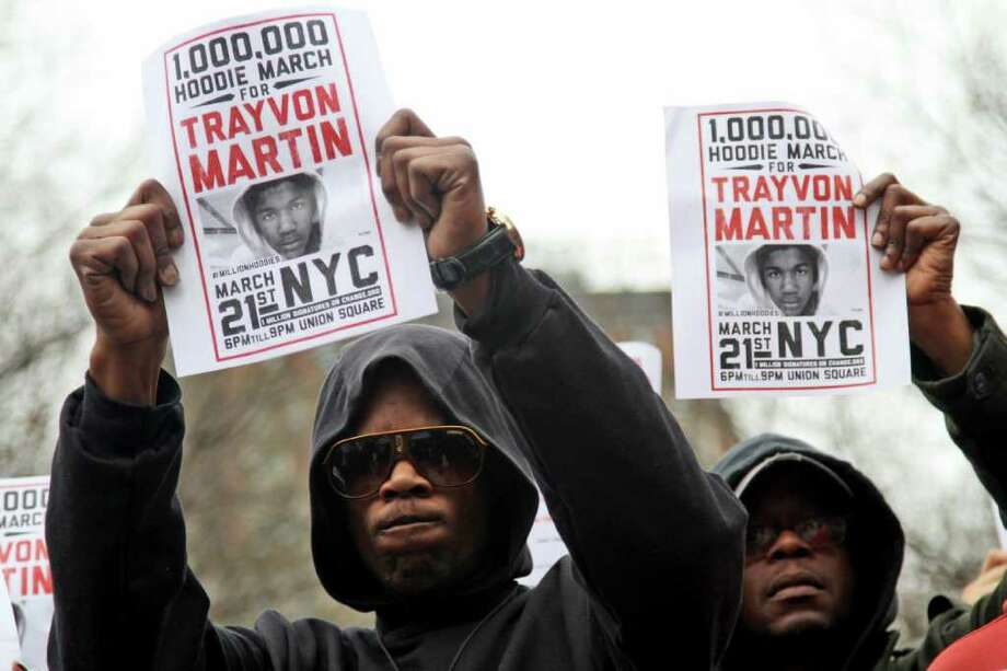 Tyrone Boykins, left, of the Brooklyn borough of New York, takes part in the Million Hoodie March in Union Square Wednesday, March 21, 2012 in New York. The march was in memory of Trayvon Martin, a black teenager shot to death by a Hispanic neighborhood watch captain in Florida. The teenager was unarmed and was wearing a hoodie. (AP Photo/Mary Altaffer) Photo: Mary Altaffer