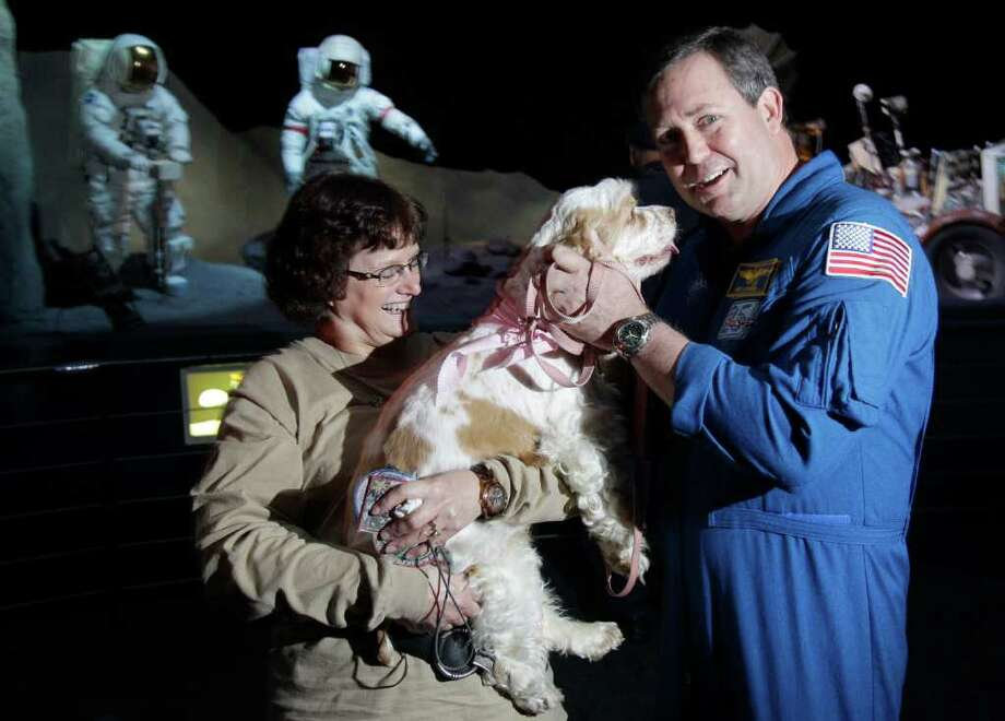 "Karen Poe, left, with Cocker Spaniel Rescue of East Texas, and NASA Astronaut Mike Foreman pose with Jenny at Space Center Houston,  Wednesday, March 21, 2012, in Houston.  Foreman volunteered to meet Jenny after reading Ken Hoffman's column about a bucket list for the dog that is dying. One of the Top 10 things on the list was to ""visit Space Center Houston and meet an astronaut."" Photo: Melissa Phillip, Houston Chronicle / © 2012 Houston Chronicle"