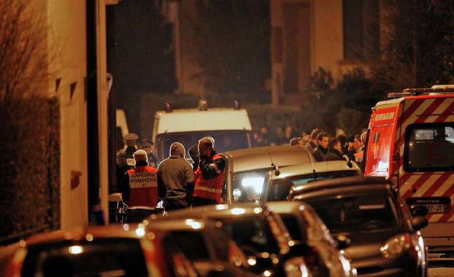 French Police officers and firefighters stand at night next to the apartment building where a suspect in the shooting at the Ozar Hatorah Jewish school is still barricaded, in Toulouse, Southern France, Wednesday, March 21, 2012. A predawn police raid on a home in Toulouse erupted into a firefight Wednesday with a gunman who claims connections to al-Qaida and is suspected of killing three Jewish schoolchildren, a rabbi and three paratroopers. (AP Photo/Christophe Ena) Photo: Christophe Ena / AP