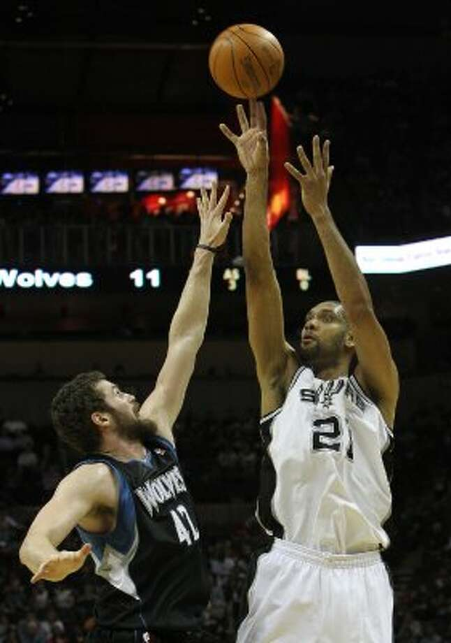 Spurs' Tim Duncan (21) shoots over Minnesota Timberwolves' Kevin Love (42) at the AT&T Center on Wednesday, Mar. 21, 2012. Kin Man Hui/Express-News. (San Antonio Express-News)