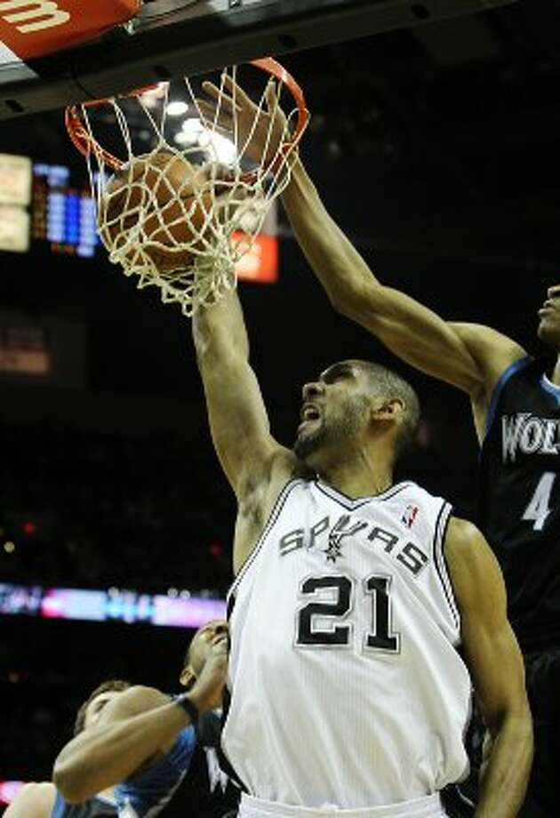 Spurs' Tim Duncan (21) dunks against Minnesota Timberwolves' Wesley Johnson (04) at the AT&T Center on Wednesday, Mar. 21, 2012. Kin Man Hui/Express-News. (San Antonio Express-News)