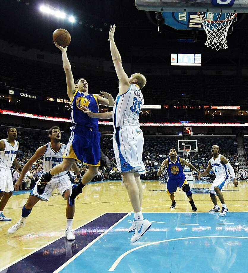 Golden State Warriors guard Klay Thompson (11) drives to the basket against New Orleans Hornets center Chris Kaman (35) in the first half of an NBA basketball game in New Orleans, Wednesday, March 21, 2012. (AP Photo/Gerald Herbert) Photo: Gerald Herbert, Associated Press