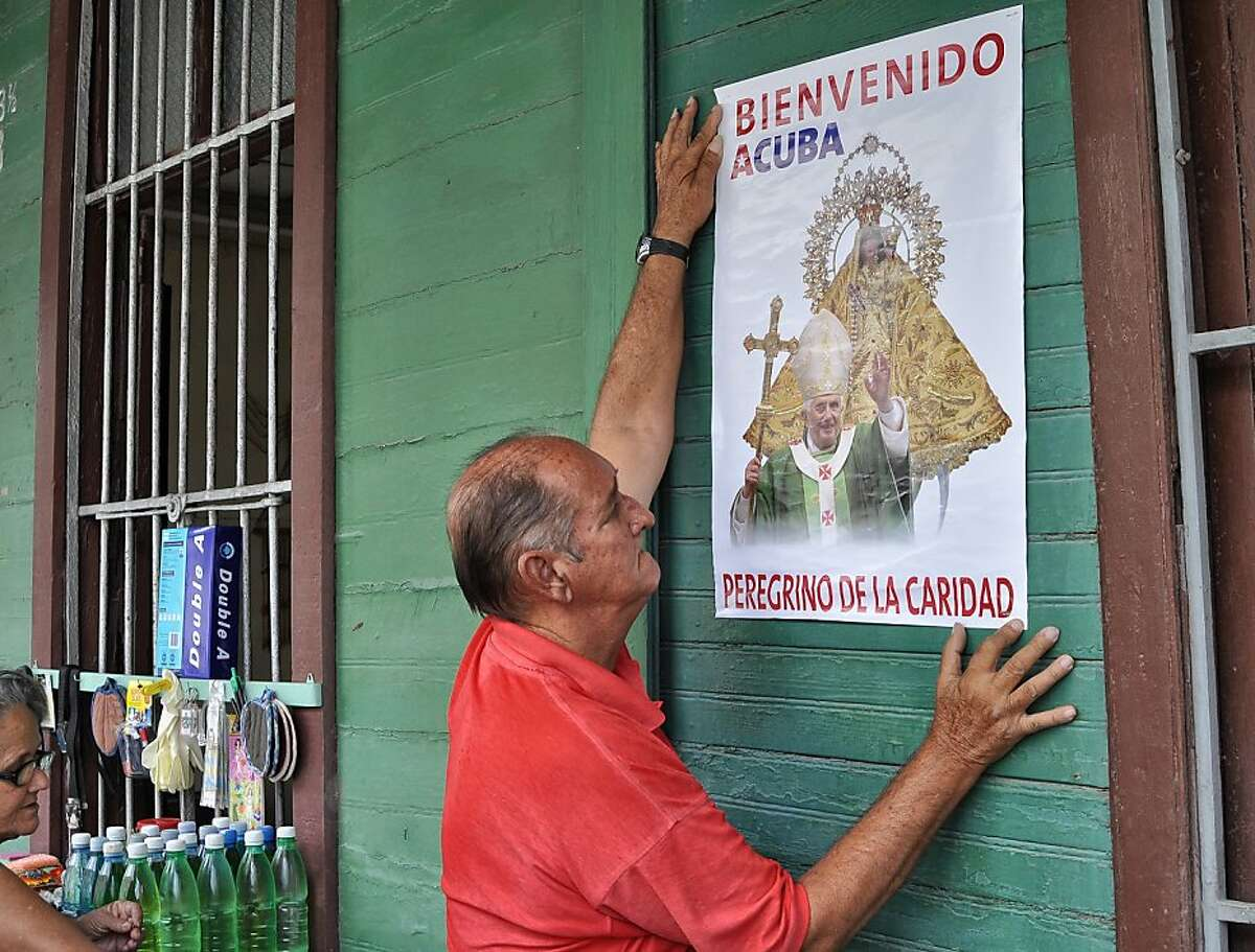A man sticks a poster welcoming Pope Benedict XVI on a store's wall in Havana on March 21, 2012. Pope Benedict XVI makes his first trip to Spanish-speaking Latin America this week in a bid to revive the Catholic faith in the region, with visits to Mexico and Cuba. The pope hopes to encourage religious fervor in the island nation where he is scheduled to arrive on March 26, and a big turnout is expected from the Catholic community -- around 10 percent of the population -- at masses in Santiago de Cuba and Havana.