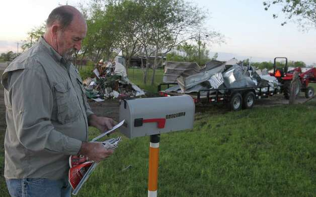 Keith Barnhill checks his mail Wednesday, March 21, 2012, at his home on Texas 173 west of Devine, after cleaning up debris scattered all over his property. Photo: John Davenport, San Antonio Express-News