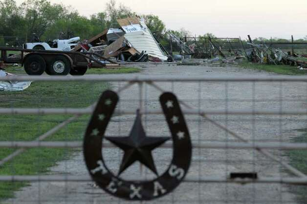 Debris is piled up behind a gate on a property on Texas 173 just west of Devine, where a tornado touched down last Monday night damaging or destroying many homes in the area. Photo: John Davenport, San Antonio Express-News / John Davenport/San Antonio Express-News