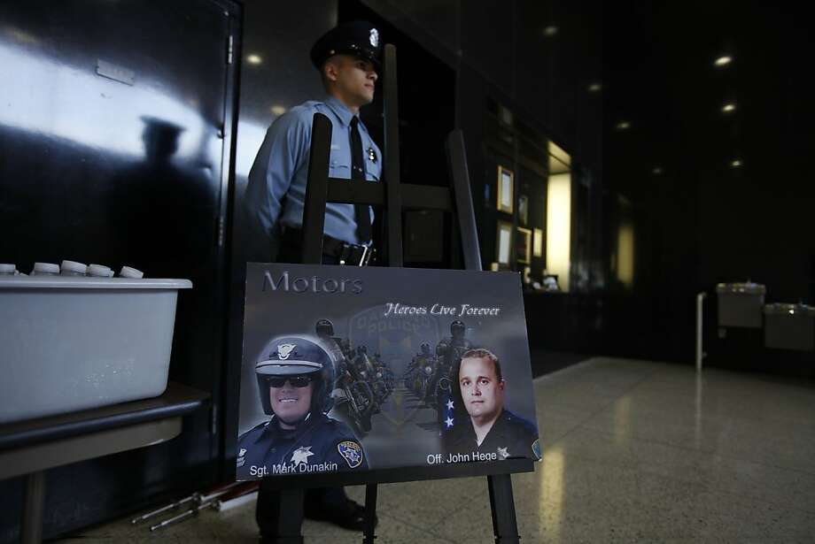 A member with the Oakland Police department stand at attention behind a photograph of fallen officer Sgt. Mark Dunakin and Officer John Hege outside the Police Administrative Building Auditorium during an I-580 freeway sign dedication ceremony in honor of fallen officers Sgt. Mark Dunakin, Sgt. Ervin RoI mans, Sgt. Daniel Sakai and Officer John Hege who died on duty in 2009 in Oakland, Calif. on Wednesday, March 21, 2012. Photo: Stephen Lam, Special To The Chronicle
